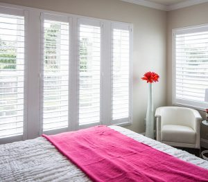 A picture of a bedroom with a set of floor-to-ceiling white shutters